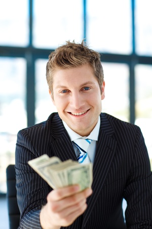 Junior businessman holding dollars and smiling at the camera photo