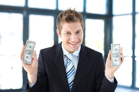 Young businessman holding money in office photo