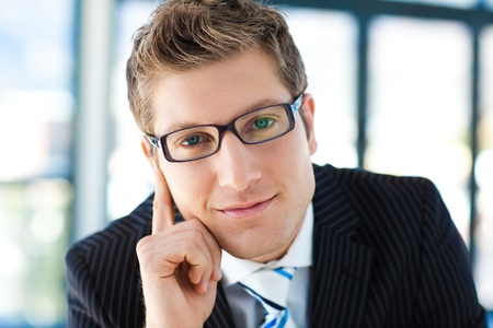 gray clothing: Junior businessman looking to the camera wearing glasses
