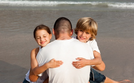 Father with his two children on the beach photo