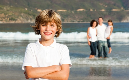 Cute boy on a beach with his parents in background Stock Photo - 10249843