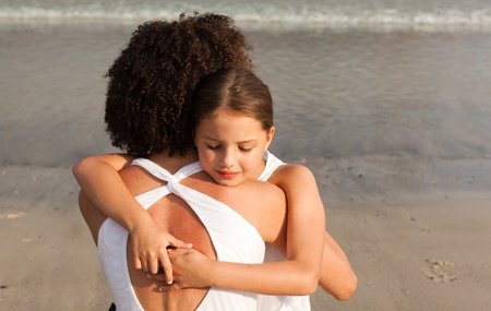 Little girl and her mother having a hug on the beach photo