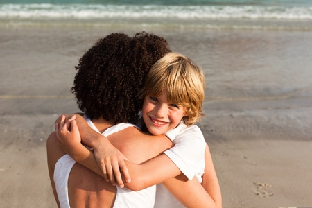Nice boy and his mother having a hug on the beach photo