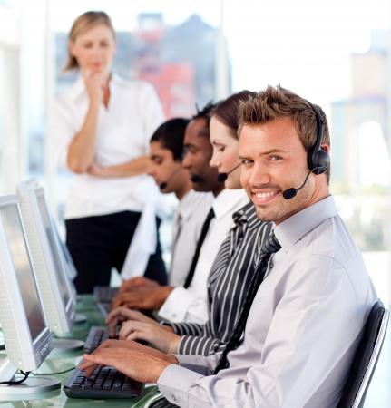 service center: Happy female leader managingher team in a call center