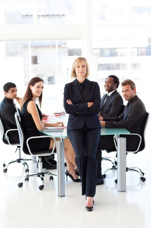 Serious businesswoman with folded arms in a meeting photo