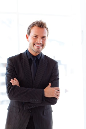 Handsome smiling businessman with folded arms photo