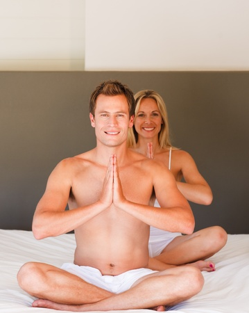 Young couple doing yoga moves on bed photo
