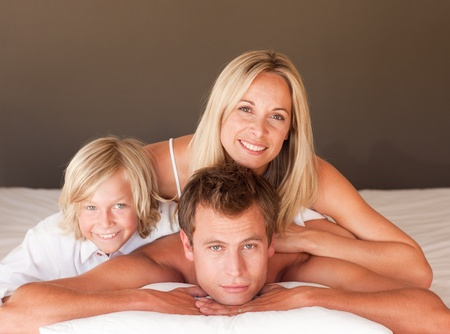 Happy couple and son enjoying together in bed  photo