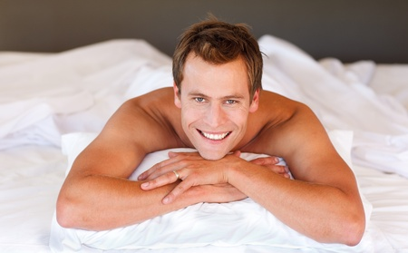 Attractive man smiling on bed photo