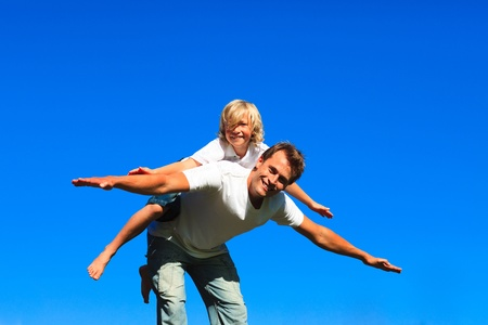 Child on father's back playing airplane Stock Photo - 10250189