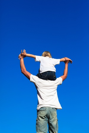 Son sitting on his fathers shoulders Stock Photo
