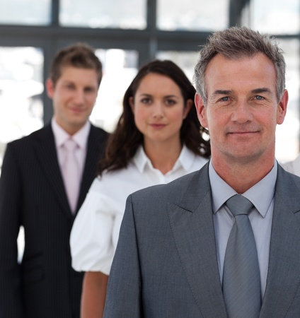 Mature businessman leading a business team in a line  photo