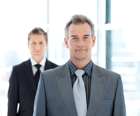 two face: Senior and young businessmen looking to the camera Stock Photo