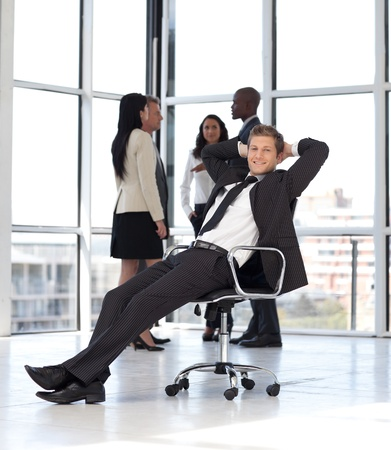 manager relaxing in office with team in background Stock Photo - 10247269