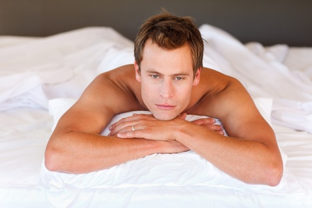 Serious handsome boy lying in bed Stock Photo - 10248733