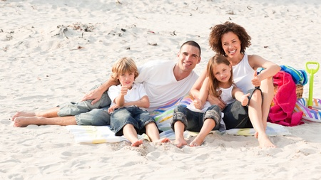 holding family together: Family playing sitting on a beach