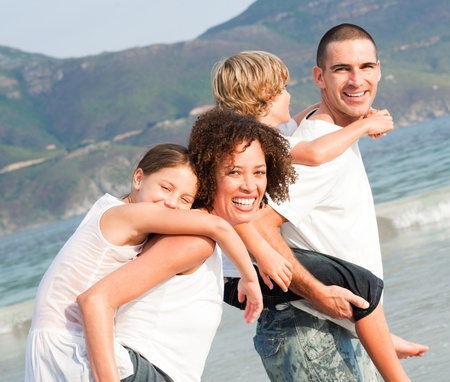 Parents giving two young children piggyback rides Stock Photo - 10245977