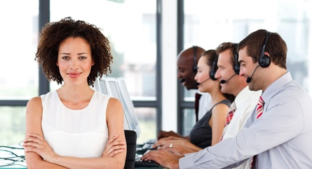 Attractive businesswoman with folded arms in a call center photo