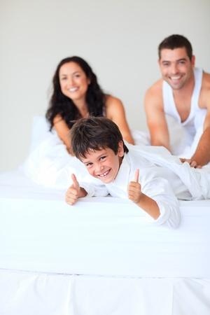 family one: Figlio con pollice in alto giocando a letto