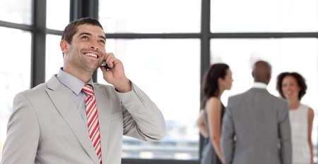 Handsome businessman on phone in office with his team photo