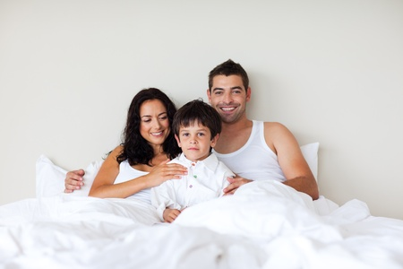 Couple and son sitting in bed photo