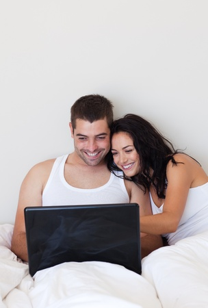 Smiling couple using a laptop in the bedroom