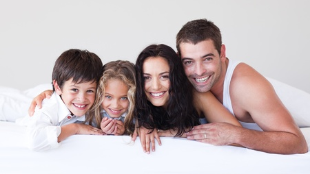 Lovely family lying on their bed Stock Photo - 10249336