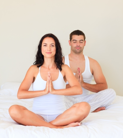 meditation room: Couple doing yoga in bed