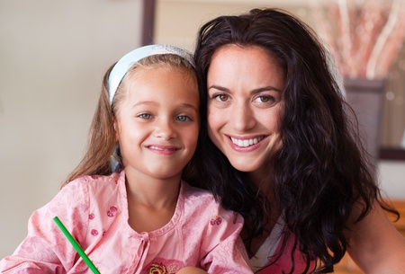Happy mother helping her daughter for homework photo