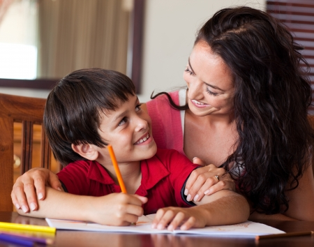 learning by doing: Radiant mother helping his son for homework Stock Photo