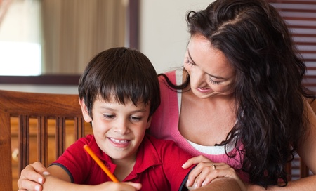 Smiling mother helping his son for homework photo