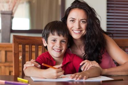 deberes: Madre feliz ayudando a su hijo para tareas