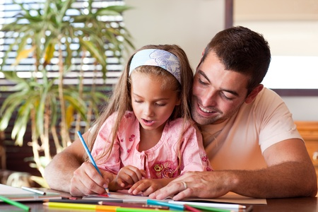 Radiant father helping her daughter for homework Stock Photo - 10250462