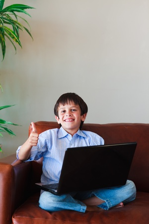 Kid using his laptop with thumb up Stock Photo - 10249840