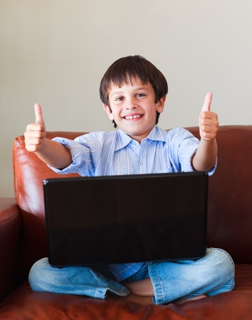 Child playing with his laptop with thumbs up photo