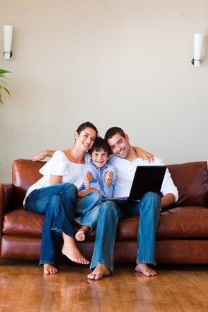Familia usando un ordenador portátil con pulgares y espacio de copia
