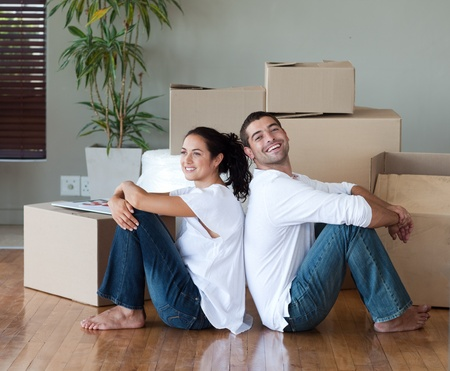 Bright couple with unpacking boxes moving to a new house photo