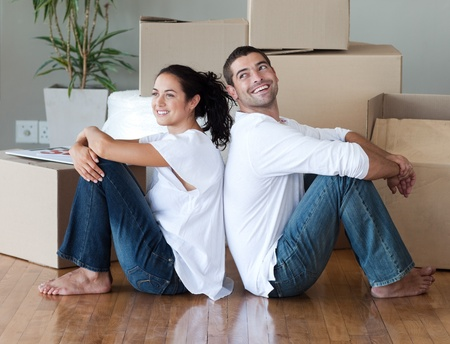 Radiant couple with unpacking boxes moving to a new house photo