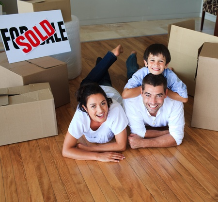Family moving house on floor smiling at the camera photo