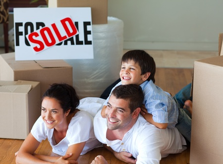 Family buying new house lying on floor photo