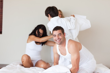 Lovely family having fun in a bedroom photo