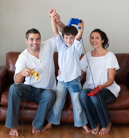 Smiling family playing video games in the living-room photo