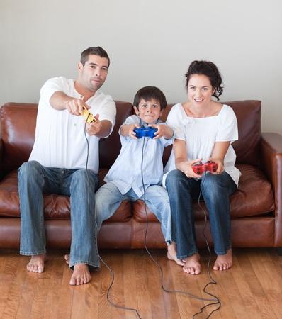 ni�os jugando videojuegos: Familia feliz jugando juegos de video en la sala de estar Foto de archivo