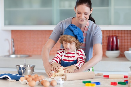 Confident mother and her son baking at home photo