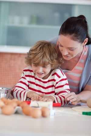 Smiling mother baking at ome with her son photo