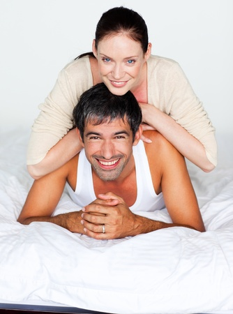 Father and mother playing in bed photo