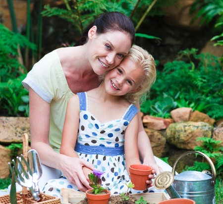 family gardening: Mother and daughter planting in their garden