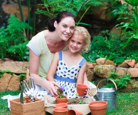 werkende moeder: Moeder en dochter planten in hun tuin
