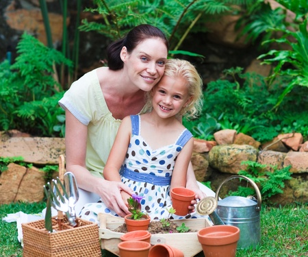home garden: Mother and daughter planting in their garden