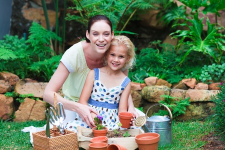 Young mother and daughter planting flowers photo